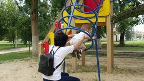 Una giovani madre e bambino stanno giocando sul campo da giuoco un giorno di estate soleggiato Famiglia felice che dipende dal ba archivi video