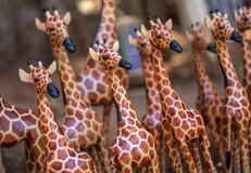 Una giraffa di legno sta fuori in folla di simili sculture Fotografia Stock Libera da Diritti