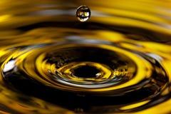Una goccia dorata di acqua Immagine Stock