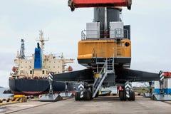 Una grúa gigante en las ruedas en el puerto transshipped los buques Foto de archivo libre de regalías