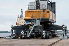 Una grúa gigante en las ruedas en el puerto transshipped los buques Foto de archivo