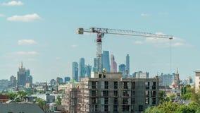 una grúa levanta la carga en el emplazamiento de la obra el día soleado con el horizonte de Moscú almacen de metraje de vídeo