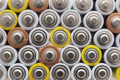 Una gran cantidad de pilas AA usadas en varios colores Imagen de archivo libre de regalías