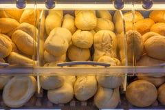 Una gran cantidad de rollos de pan producidos industrialmente en una panadería imagenes de archivo