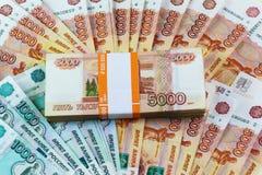 Una gran cantidad de rublos rusas se dispersa en la tabla imagen de archivo