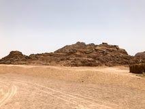 Una grande alta montagna sabbiosa di pietra nel deserto con il fondo della sabbia Fotografie Stock