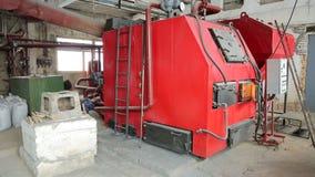 Una grande caldaia per il riscaldamento degli stabilimenti industriali con i combustibili alternativi ed i sostegni di legno stock footage