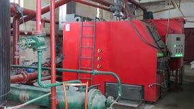 Una grande caldaia per il riscaldamento degli stabilimenti industriali con i combustibili alternativi ed i sostegni di legno archivi video
