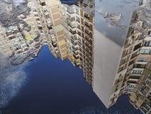 Una grande costruzione di appartamento alta con molti pavimenti è riflessa in una pozza di colore blu, vecchia neve come una nuvo Fotografia Stock