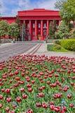 Una grande costruzione rossa con le colonne sulla facciata contro un cielo blu con le nuvole bianche, davanti alla costruzione è  Fotografie Stock