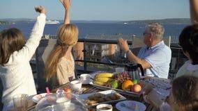 Una grande famiglia felice cena sul terrazzo aperto ed ondeggia le sue mani che passano in traghetto del mare stock footage