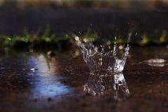 Una grande goccia di pioggia colpisce la terra fotografie stock