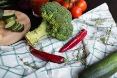 Una grande inflorescenza dei broccoli, una zucca verde e due peperoncini rossi stanno trovando sul tessuto del plaid Nell'archivi Fotografie Stock
