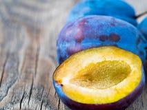 una grande prugna dolce blu e una metà tagliata su un legno Fotografia Stock