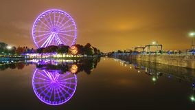 Una grande ruota panoramica a Montreal efficacemente è riflessa nell'acqua Città di notte immagine stock
