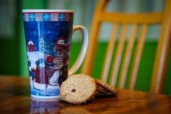 Una grande tazza di tè con la decorazione del pupazzo di neve e su un biscu del tè fotografia stock