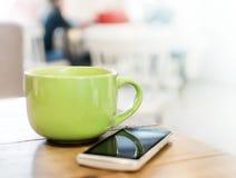 Una grande tazza verde con una bevanda e uno smartphone su una tavola di legno in un caffè fotografia stock libera da diritti