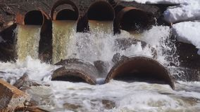 Una grande, vecchia tromba fatta di ferro Da scorre l'acqua nel fiume a volte sporco e nocivo archivi video