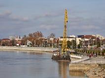 Una gru gialla su una chiatta sta stando sul pilastro del fiume di Kuban vicino all'argine della città di Krasnodar fotografia stock