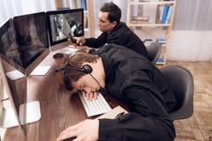 Una guardia dell'uomo sta dormendo nel posto di lavoro fotografia stock