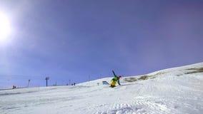Una guida dell'uomo su un pendio su uno snowboard, eseguente un trucco Stazione sciistica nelle alpi stock footage