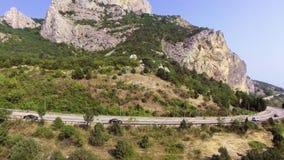 Una guida di veicoli lungo la strada della montagna sulla costa di mare stock footage