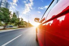 Una guida di veicoli su un'autostrada alle alte velocità Fotografia Stock