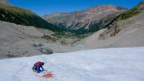 Una guida maschio della montagna che installa un sistema di carrucole per il salvataggio del crepaccio su un ghiacciaio Fotografia Stock