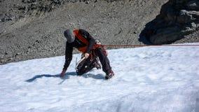Una guida maschio della montagna che installa un sistema di carrucole per il salvataggio del crepaccio su un ghiacciaio Fotografia Stock Libera da Diritti