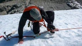 Una guida maschio della montagna che installa un sistema di carrucole per il salvataggio del crepaccio su un ghiacciaio Fotografie Stock Libere da Diritti
