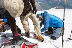 Una guida professionale vi aiuta ad installare e vestire i ramponi dell'alpinista Fotografie Stock