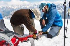 Una guida professionale vi aiuta ad installare e vestire i ramponi dell'alpinista Immagini Stock