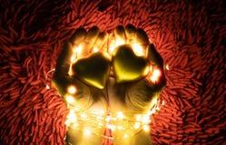 Una guirnalda caliente de la luz del color que rodea dos manos que llevan a cabo corazones Día del `s de la tarjeta del día de Sa imágenes de archivo libres de regalías
