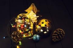 Una guirnalda que brilla intensamente en un tarro de cristal y decoraciones de la Navidad en un fondo de madera oscuro Año Nuevo, Fotos de archivo