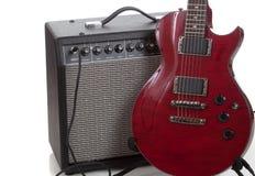 Una guitarra eléctrica con un amperio negro en un fondo blanco Imagen de archivo libre de regalías