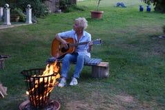 Una guitarra es parte de una hoguera de la tarde fotos de archivo libres de regalías