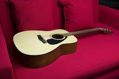 Una guitarra puesta en el sofá rojo Imágenes de archivo libres de regalías