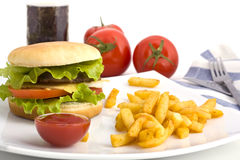 Una hamburguesa con las fritadas en una placa blanca Fotografía de archivo libre de regalías