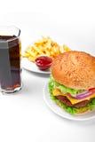 Una hamburguesa con las fritadas, la salsa de tomate y la cola Fotos de archivo libres de regalías