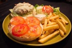 Una hamburguesa de la carne y del queso sirve con las fritadas fotos de archivo libres de regalías