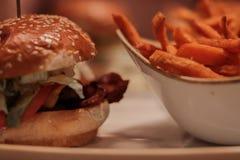 Una hamburguesa del deliciouse con las fritadas dulces del potaot closezup, papel pintado, asado, carne de vaca, salat; imagen de archivo