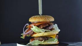 Una hamburguesa grande jugosa con un bollo doble y una chuleta doble con verdes y las verduras sujetadas con grapa con un cuchill metrajes
