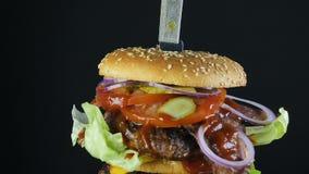 Una hamburguesa grande jugosa con un bollo doble y una chuleta doble con verdes y las verduras sujetadas con grapa con un cuchill almacen de video