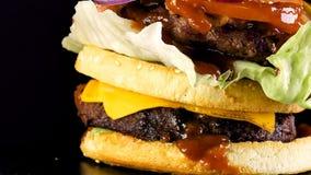 Una hamburguesa grande jugosa con un bollo doble y una chuleta doble con verdes y las verduras sujetadas con grapa con un cuchill almacen de metraje de vídeo