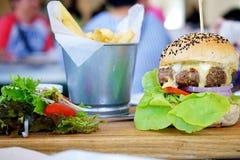 Una hamburguesa jugosa de la carne de vaca con el queso derretido servido con la ensalada y las patatas fritas se coloca en table Imagenes de archivo