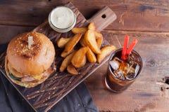 Una hamburguesa sabrosa con bocados bajo la forma de patatas con la salsa de ajo blanca y un vidrio de cola fría hamburguesa jugo Imagen de archivo libre de regalías
