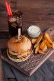 Una hamburguesa sabrosa con bocados bajo la forma de patatas con la salsa de ajo blanca y un vidrio de cola fría hamburguesa jugo Imagenes de archivo