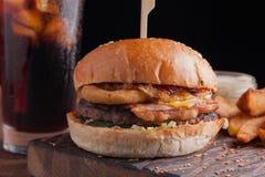 Una hamburguesa sabrosa con bocados bajo la forma de patatas con la salsa de ajo blanca y un vidrio de cola fría hamburguesa jugo Fotos de archivo libres de regalías