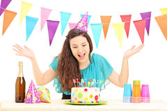Una hembra del feliz cumpleaños con un sombrero del partido que gesticula con su mano Fotos de archivo