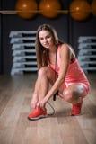 Una hembra hermosa que lleva deportes rosados uniforma en un fondo del gimnasio Aptitud, actividad, y concepto del levantamiento  Fotografía de archivo